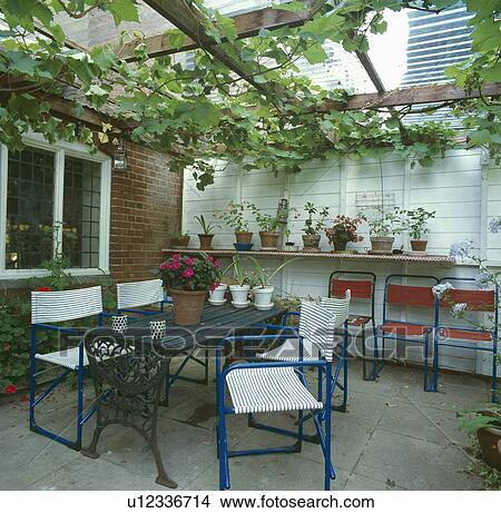 Metal Table And Chairs In Conservaory Extension With Grapevine Growing On  Pergola