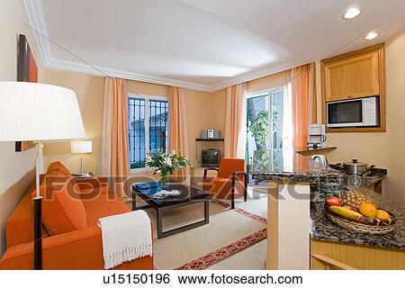 Modernes, hotel, livingroom, mit, orange, sofa, und, klein, kueche Stock  Fotograf