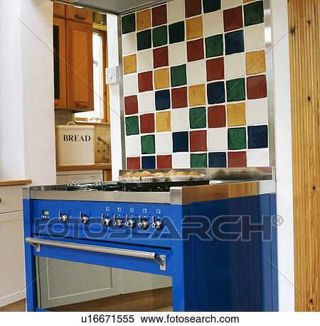 Stock Image of Multi-coloured tiles above bright blue modern oven in on shaped tiles, design tiles, dry tiles, grey tiles, recycled tiles, painted tiles,