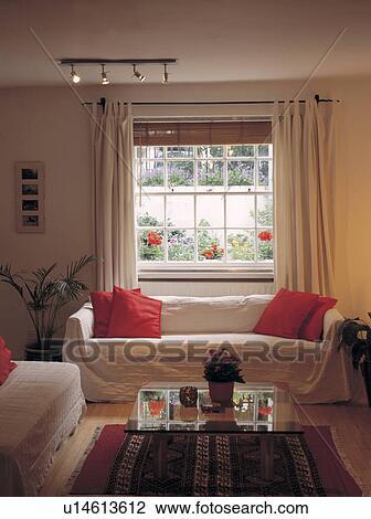 Stock foto orange kissen und creme werfen auf sofa - Sofa vor fenster ...