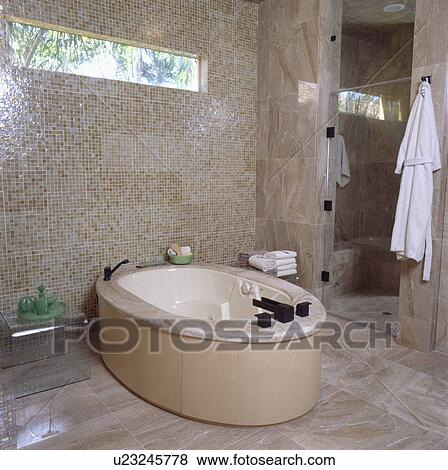 Oval Freestanding Bath In Modern Bathroom With Beige Mosaic Tiled Wall Stock Photo