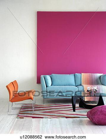 Stock Photo of Pastel blue sofa against bright pink picture in ...