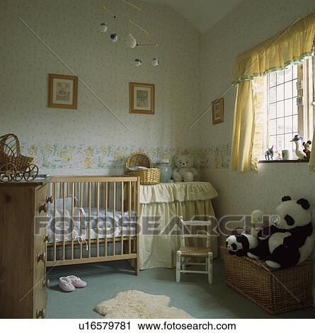 pastel gele gordijnen en patterned behangen in baby babykamer met houten kinderbed en klein witte stoel