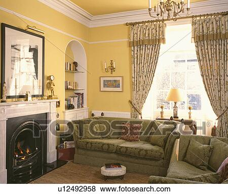 Patterned curtains and green sofas beside fireplace in yellow livingroom  Stock Photo
