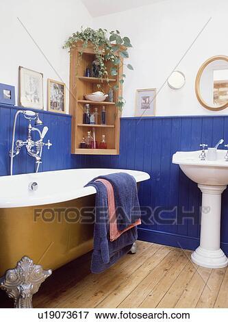 Plancher bois, et, or, clawfoot, bain, dans, traditionnel, salle bains, à,  bleu clair, lambris, à, dado, hauteur Banque de Photo