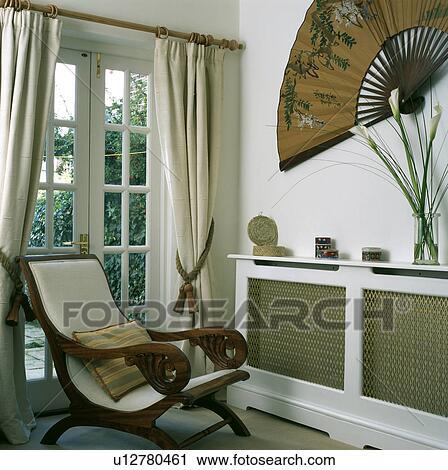 Planter\'s, stuhl, vor, französische fenster, mit, creme, vorhänge, in,  wohnzimmer, mit, groß, chinesischer, fächer, auf, wand, oben, heizkörper,  mit, ...