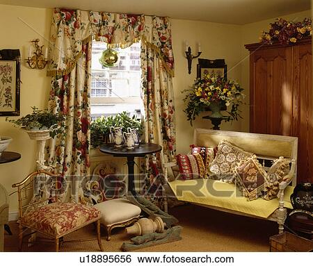 Traditional yellow cottage living room with floral curtains and tapestry  cushions on sofa Stock Photograph