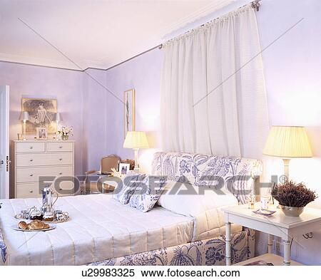 White drapes above blue+white upholstered bed with white ...