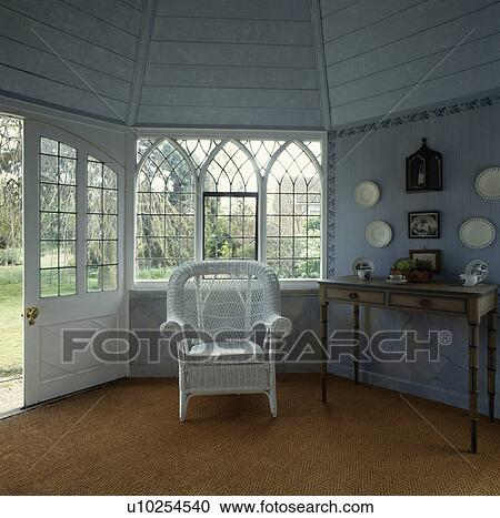 Stock Photography of White wicker armchair in front of Gothic style