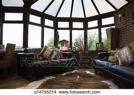 Animalprint Cushions On Black Leather Sofas In Conservatory Living Room