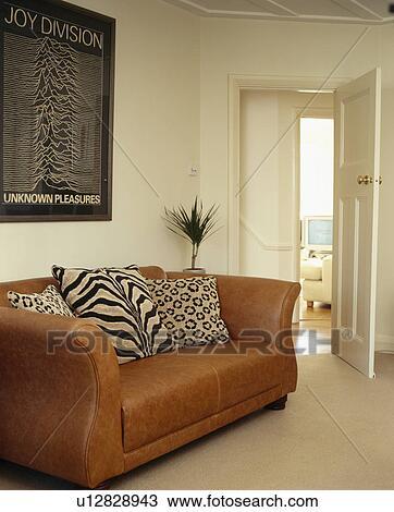 Animalprint Cushions On Brown Leather Sofa In Cream Living Room Stock Image