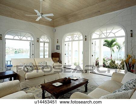 Ansicht, von, dass, meer, durch, groß, gewölbt, französische türen, in,  karibisch, wohnzimmer, creme, sofas, und, hölzern, decke Stock Bild