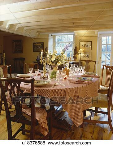 Antique Chairs And Pink Checked Cloth With Place Settings On Table In  Country Dining Room With Stripped Ceiling Beams