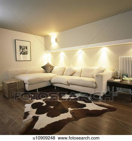 Artificial cowhide rug in modern living room with ...