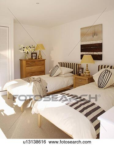 Black and white striped throws on single beds in modern ...