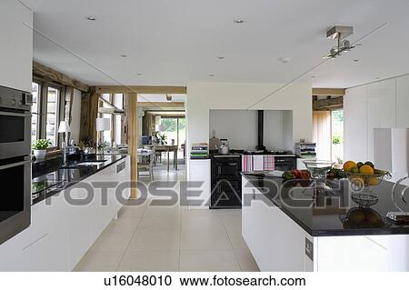 Black Granite Worktop On Island Unit In Modern White Barn Conversion Kitchen With Limestone Flooring