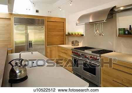 Chrome Kettle On Island Unit In Modern Kitchen With Stainless Steel Range Oven