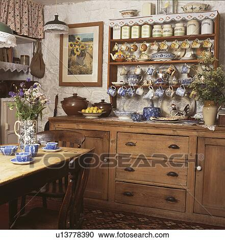 Collection Of China On Shelves Above Pine Dresser In Country Kitchen