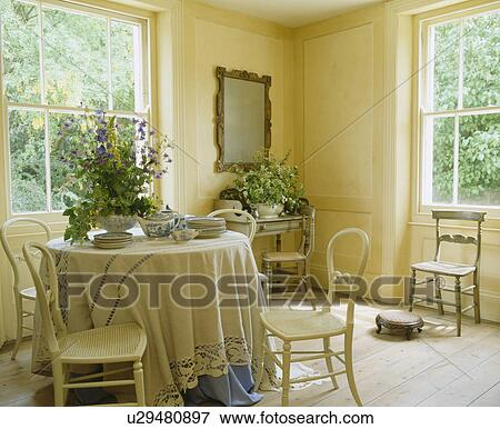 Cream painted antique chairs at circular table with cream cloth in elegant  cream dining room with wooden flooring - Picture Of Cream Painted Antique Chairs At Circular Table With Cream