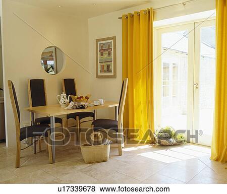 gele gordijnen en kalksteen bevloering in hippe eetkamer