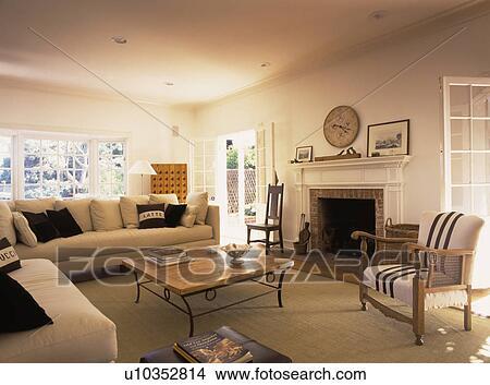 Groß, creme, sofas, und, sisal, teppich, in, neutral, wohnzimmer, mit,  gestreift, sessel, neben, kaminofen Bild