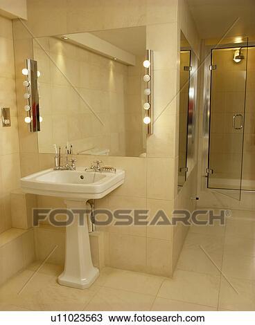 Lighted Mirror Above White Pedestal Basin In Modern Bathroom