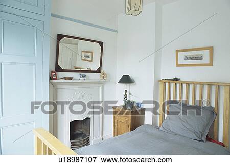 Miroir, au-dessus, cheminée, dans, petit, blanc, chambre à coucher, à,  gris, bedlinen, sur, lit bois Banque de Photo