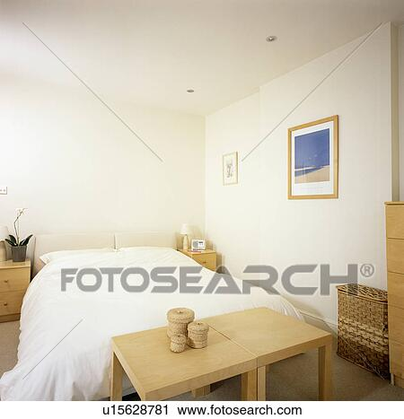 Pair Of Simple Pale Wood Tables Below Bed With White Bedlinen In  Economy Style Bedroom