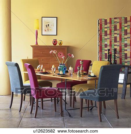Pink And Turquoise Upholstered Dining Chairs At Table In Modern Yellow Dining Room Stock Image U12623582 Fotosearch