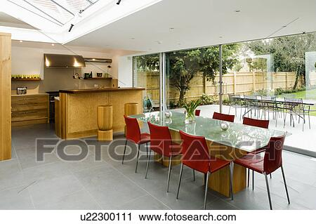 Red Chairs And Glass Table In Large Modern Kitchen Dining Room With Grey Flooring And View Of The Garden Stock Image U22300111 Fotosearch
