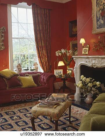 Red Velour Sofa In Front Of Window With Patterned Red Curtains In