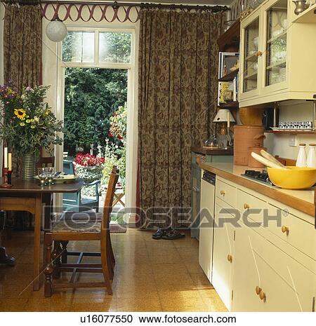 Semplice, tavola legno, e, sedie, in, cucina, con, sughero, pavimento, e, modellato, tenda, a, windows francese Archivio Immagini