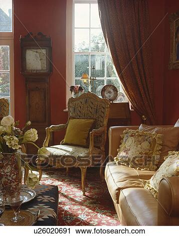 Tapestry Cushions On Cream Leather Sofa In Cosy Living Room With Red Curtains And Antique Upholstered Chair Stock Image