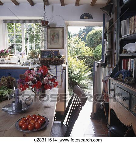 White cottage kitchen with flowers on the table and door ...