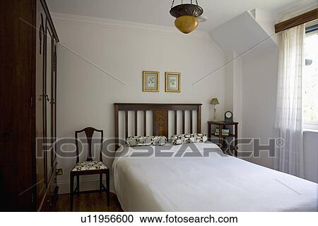 Stock Photography White Linen On Bed In Small Uncluttered Bedroom Fotosearch Search