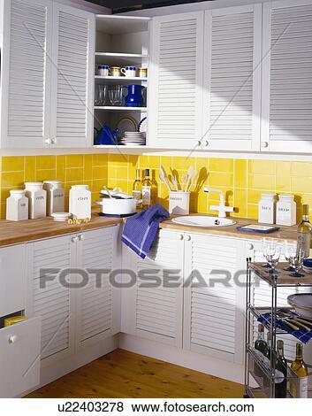 Witte Keramisch Opslag Stopflessen Op Worktop Van Economie Keuken Met Gele Muur Tegels En Kasten Met Witte Louvre Deuren Stock Foto