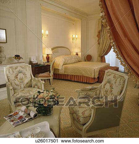 18th century-style armchairs in large townhouse bedroom with ...