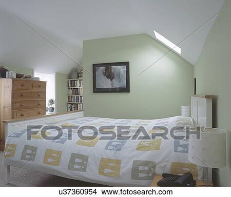 abstracte patterned witte dekbed in pastel groene woonstudio conversie slaapkamer met groot dennenboom ladenkast