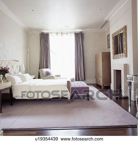 Bed with white bedlinen in bedroom with large mauve rug and ...