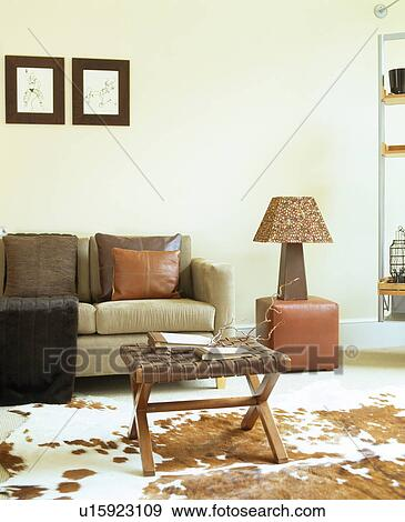 Beige Sofa In Modern White Living Room With Faux Ponyskin Rug