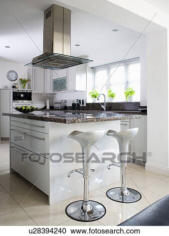 A Stools At Island Unit In Large Modern White Kitchen Extension