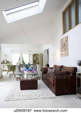Brown leather sofa and ottoman in large white living room with cream cotton  rug Stock Photo