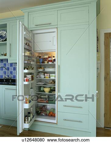 Close-up of fridge-freezer with open door in pastel green kitchen storage  unit Stock Image