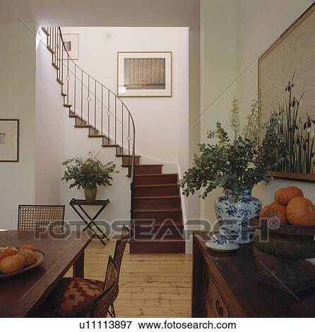 Console Table And Dining Chairs In Modern Hall With Curved Wooden Stairs