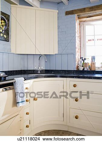 Cream corner cupboard above sink in pale blue country kitchen with cream fitted cupboards and units & Stock Photo of Cream corner cupboard above sink in pale blue country ...