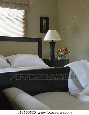 Cream Lamp On Table Beside Bed With White Pillows In Modern Monochromatic Bedroom Stock Image U16560520 Fotosearch