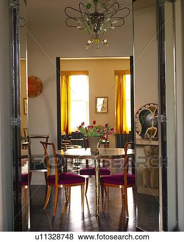 Double Doors Open To Antique Table And Chairs In Traditional Dining Room With Polished Parquet Floor
