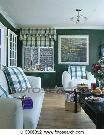 Grün, kariert, kissen, weiß, sofa, und, sessel, in, dunkles grün,  wohnzimmer, mit, grün, kariert, blenden, und, hölzerner stock Stock Bild
