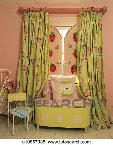 Green curtains and pink shutters in child\'s pink bedroom Stock Photo