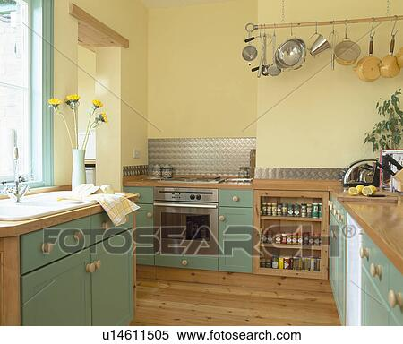 Green Ed Units In Modern Pastel Yellow Kitchen With Saucepans On Hanging Wall Rack